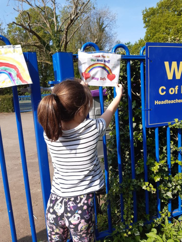 Sophie adding her poster to our school gates