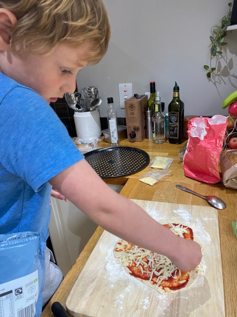 Using those fine motor skills when making pizza